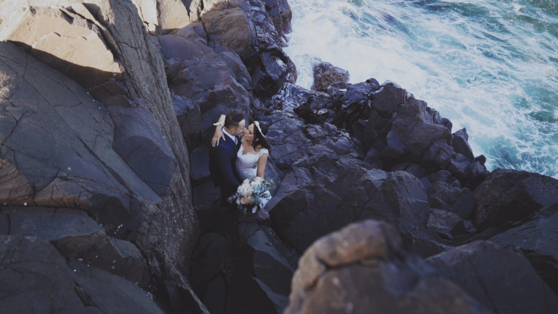 Bride and groom on rocks in bombo wedding